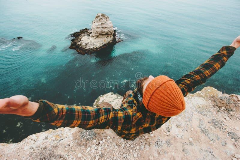 Sirva la sentada aumentada las manos del viajero en el acantilado sobre el mar foto de archivo
