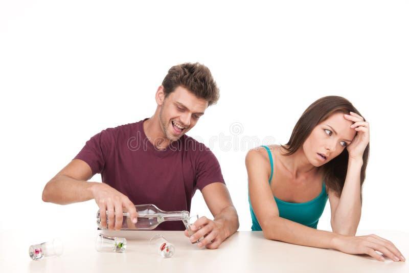 Sirva la sentada de colada del alcohol y de la mujer trastornada en la tabla imagen de archivo
