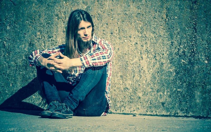 Sirva la sentada de pelo largo solamente triste en la pared del grunge imágenes de archivo libres de regalías