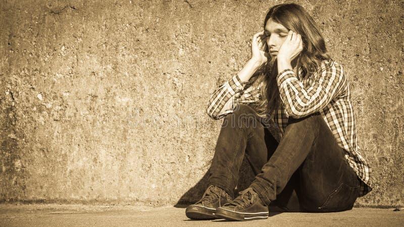 Sirva la sentada de pelo largo solamente triste en la pared del grunge foto de archivo