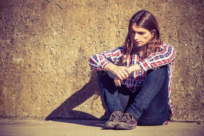 Sirva la sentada de pelo largo solamente triste en la pared del grunge imagenes de archivo