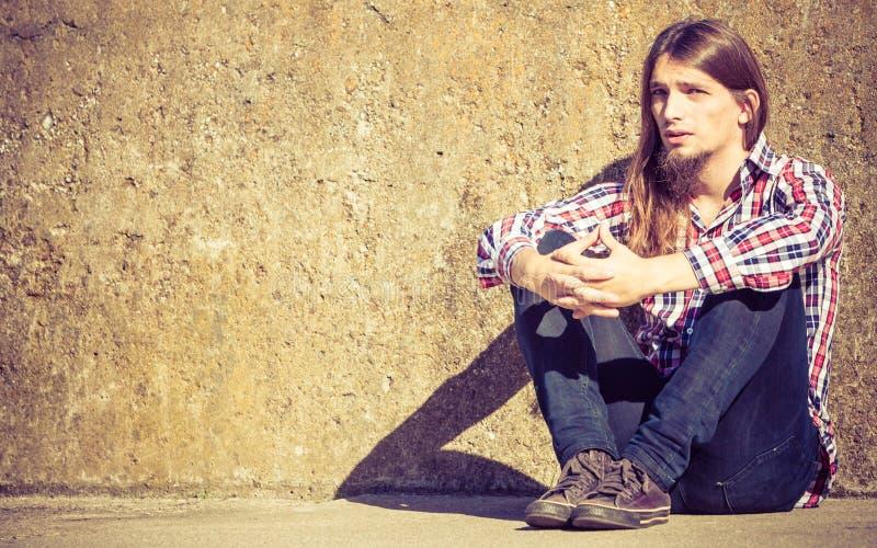 Sirva la sentada de pelo largo solamente triste en la pared del grunge imagen de archivo