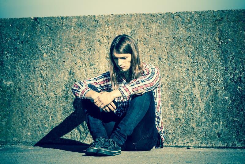 Sirva la sentada de pelo largo solamente triste en la pared del grunge fotografía de archivo libre de regalías
