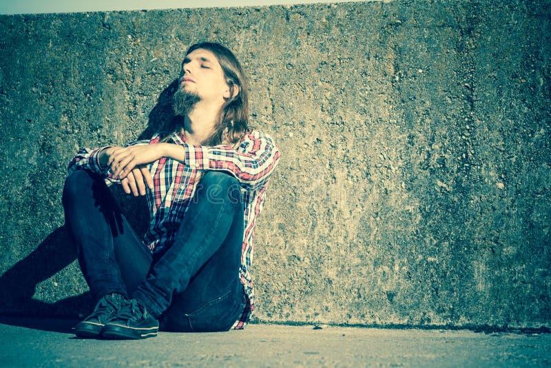 Sirva la sentada de pelo largo solamente triste en la pared del grunge imagen de archivo libre de regalías