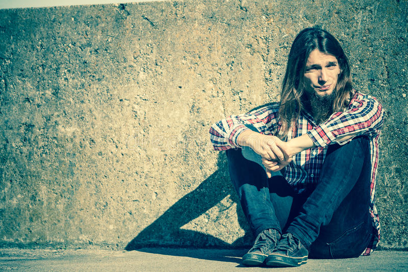 Sirva la sentada de pelo largo solamente triste en la pared del grunge fotografía de archivo