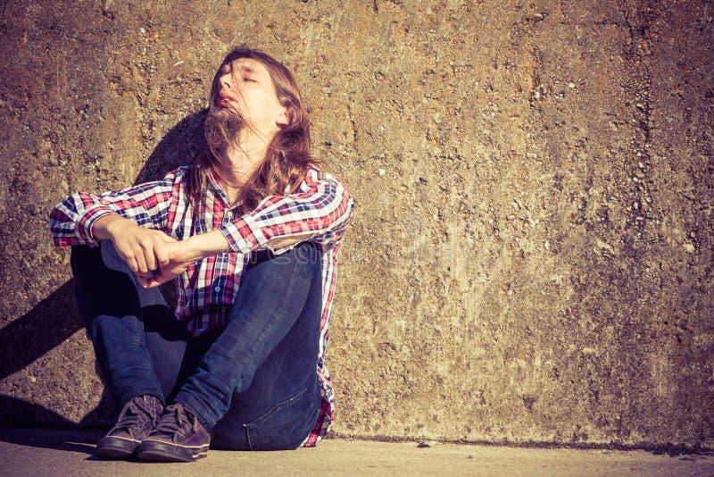Sirva la sentada de pelo largo solamente triste en la pared del grunge foto de archivo libre de regalías