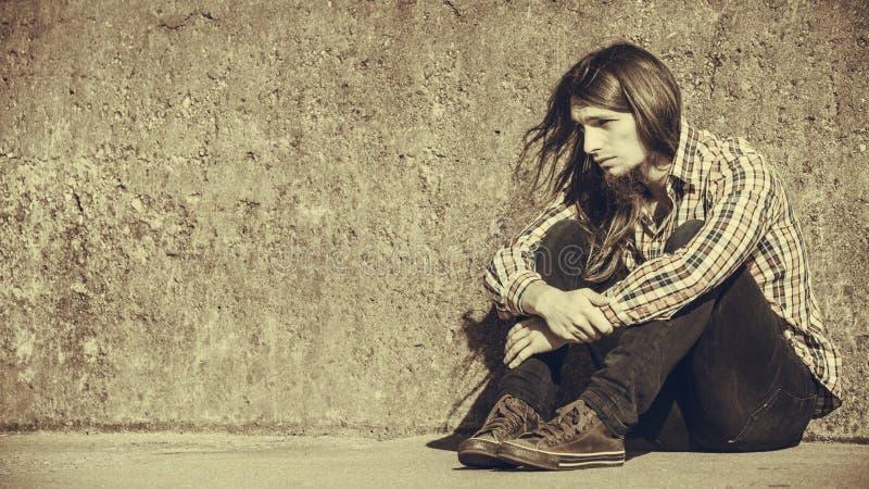 Sirva la sentada de pelo largo solamente triste en la pared del grunge fotos de archivo