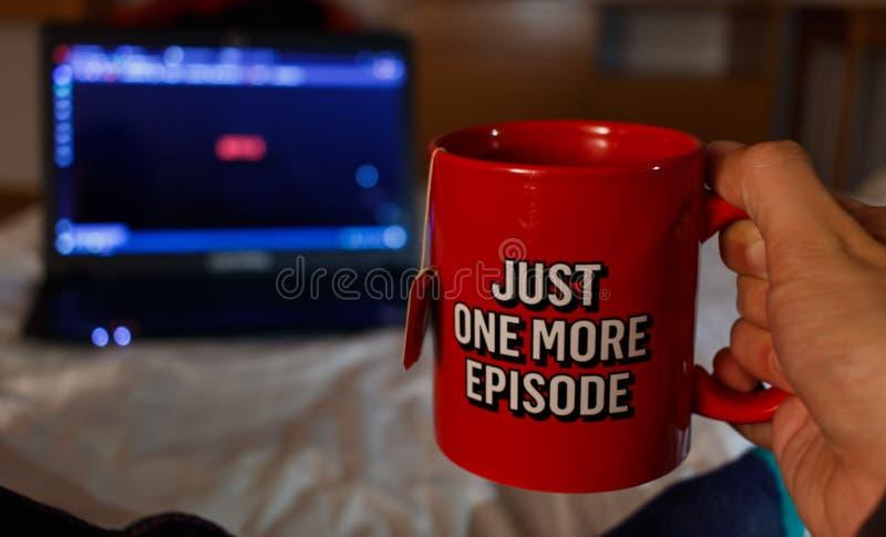 Sirva la serie de observación mientras que se sostiene con una taza de té con el netfix foto de archivo