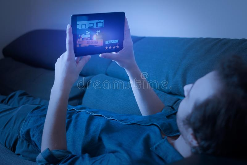 Sirva la serie televisiva de observación en fluir con la tableta digital fotos de archivo libres de regalías