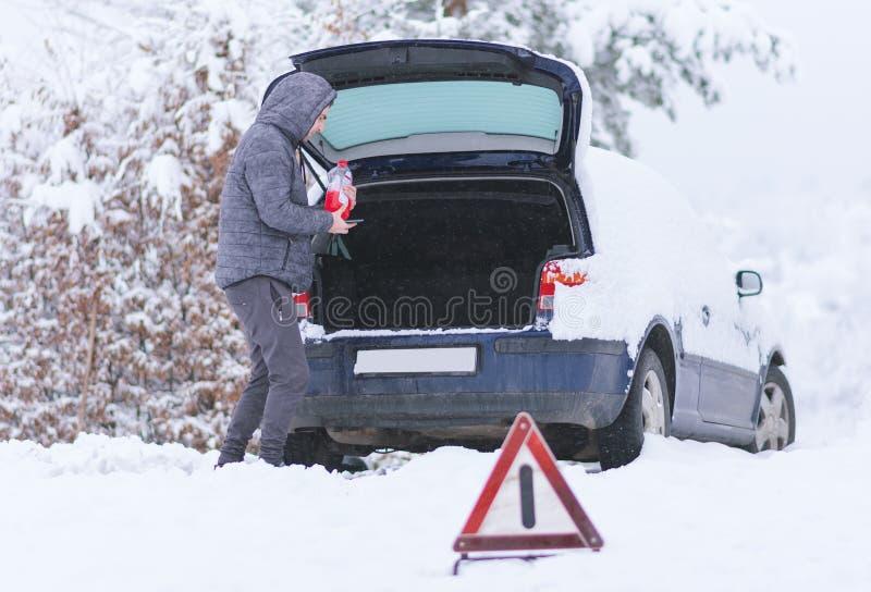 Sirva la situación delante del coche dañado que lleva a cabo la botella de antifreez imágenes de archivo libres de regalías
