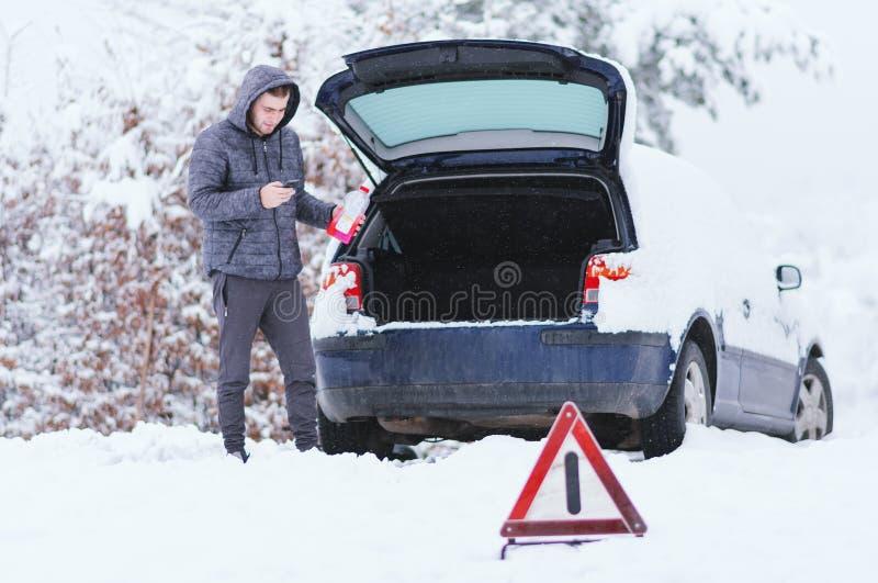 Sirva la situación delante del coche dañado que lleva a cabo la botella de antifreez imagen de archivo libre de regalías