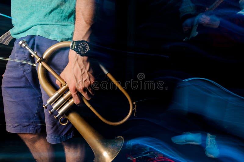 Sirva la situación en el club de noche con una trompeta en su mano imagen de archivo