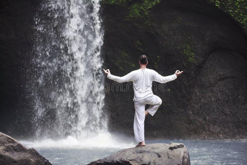 Sirva la situación en yoga de la meditación en roca en la cascada foto de archivo
