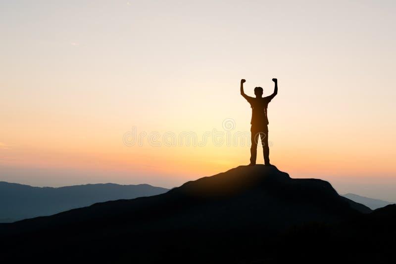 Sirva la situación encima de la montaña en el fondo de la puesta del sol, silueta fotografía de archivo