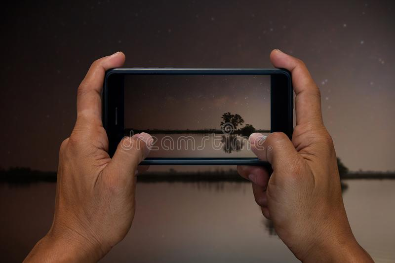 Sirva la tenencia de la mano y lago móvil con, el teléfono celular, la fotografía elegante del teléfono y en la noche con las est fotografía de archivo
