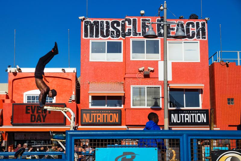 Sirva las figuras del entrenamiento delante del edificio anaranjado de la playa del músculo en la playa de Venecia, Los Ángeles,  foto de archivo