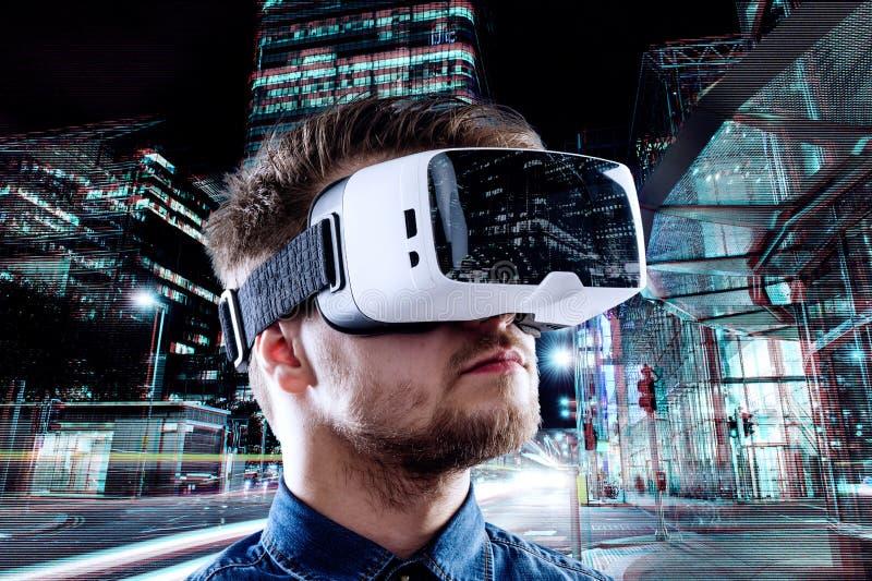 Sirva las gafas de la realidad virtual que llevan contra ciudad de la noche fotos de archivo