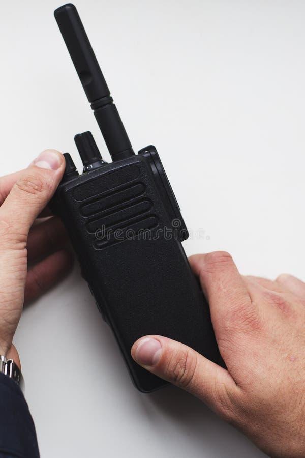 Sirva las manos del ` s que sostienen el Walkietalkie portátil negro fotos de archivo