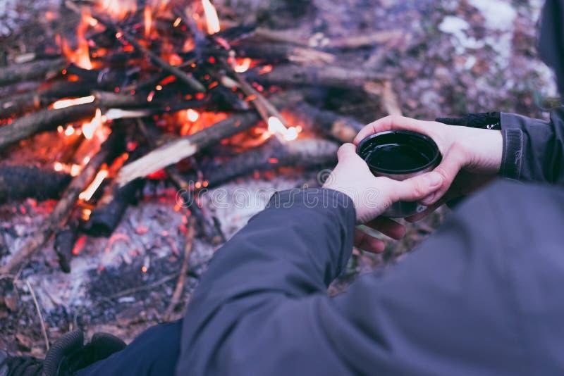 Sirva las manos del viajero que sostienen la taza cerca del fuego fotografía de archivo libre de regalías