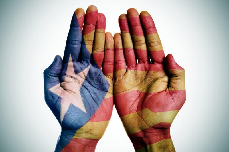 Sirva las manos modeladas con la bandera catalana de la favorable-independencia foto de archivo