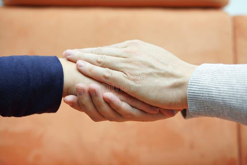 Sirva las manos que llevan a cabo la mano de la mujer de ambos lados compasión foto de archivo