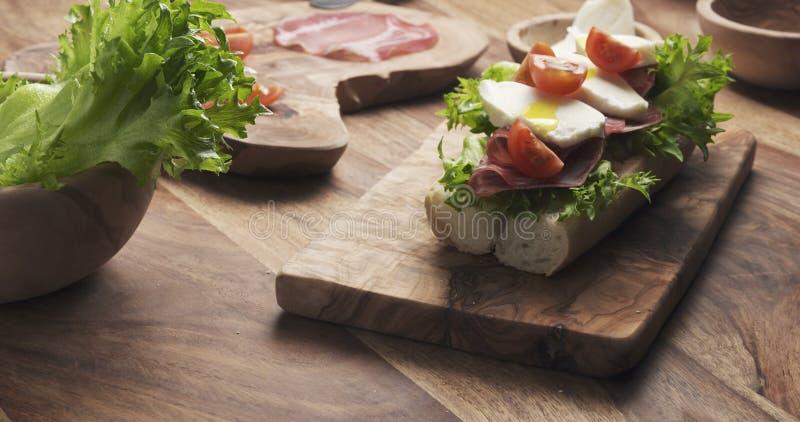 Sirva las manos que preparan el bocadillo italiano con el prosciutto y la mozzarella fotografía de archivo