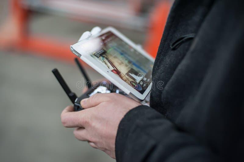 Sirva las manos que sostienen el transmisor y que controlan el abejón de FPV fotografía de archivo libre de regalías