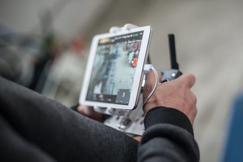 Sirva las manos que sostienen el transmisor y que controlan el abejón de FPV imagenes de archivo