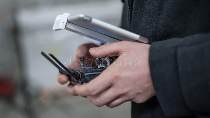 Sirva las manos que sostienen el transmisor y que controlan el abejón de FPV imagen de archivo