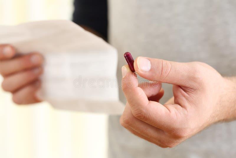 Sirva las manos que sostienen una píldora y que leen el prospecto imagen de archivo