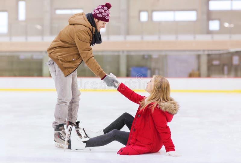 Sirva a las mujeres de ayuda para alzarse en pista de patinaje foto de archivo libre de regalías