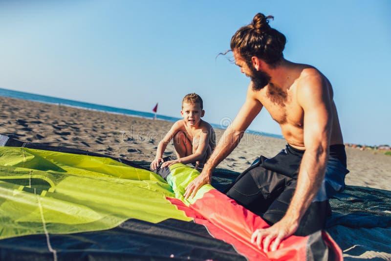 Sirva a las personas que practica surf con su hijo en wetsuits con el equipo de la cometa fotos de archivo libres de regalías