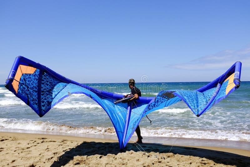 Sirva a las personas que practica surf en wetsuits con el equipo de la cometa para practicar surf, en Sabaudia, Lazio, Italia imagen de archivo libre de regalías