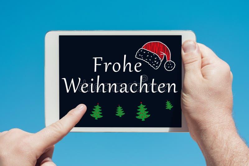 Sirva llevar a cabo un dispositivo de la tableta con el texto en Feliz Navidad del ` del ` alemán de Frohe Weihnachten y el tacto fotografía de archivo libre de regalías
