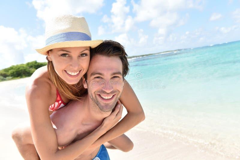 Sirva llevar a su novia encendido detrás en la playa del Caribe foto de archivo
