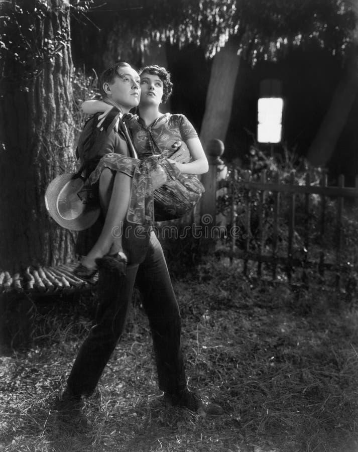 Sirva llevar a una mujer en sus brazos a través de un patio trasero (todas las personas representadas no son vivas más largo y ni fotografía de archivo