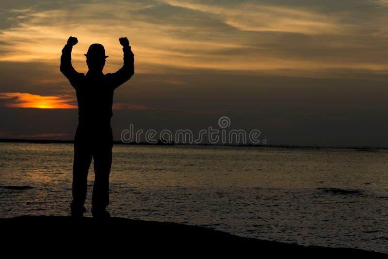Sirva los brazos aumentados en la playa bajo tiempo del crepúsculo de la puesta del sol fotos de archivo libres de regalías