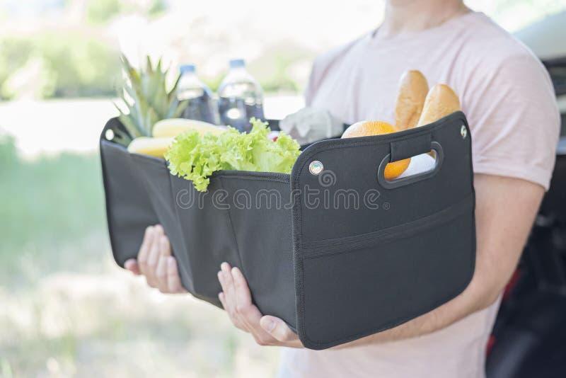 Sirva los controles en su cesta negra grande del bolso de las manos por completo de productos fotografía de archivo libre de regalías