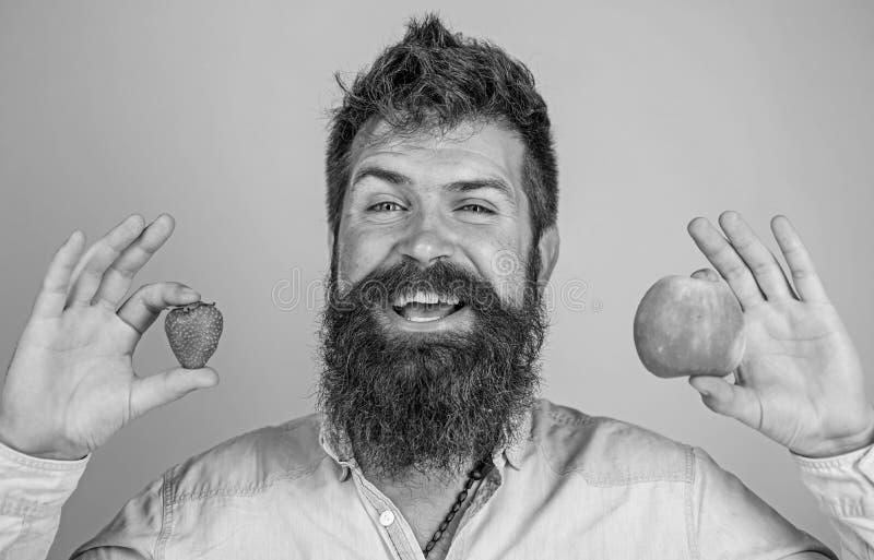 Sirva los controles sonrientes barbudos manzana y fresa en fondo del azul de las manos Concepto de la nutrici?n de la fruta de la foto de archivo libre de regalías