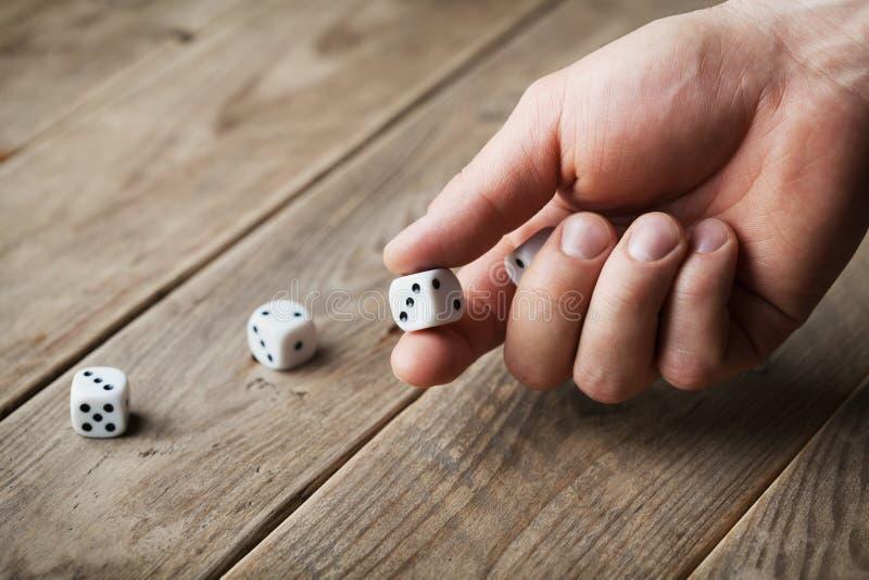Sirva los dados blancos que lanzan de la mano en la tabla de madera Dispositivos de juego Juego del concepto de azar fotos de archivo