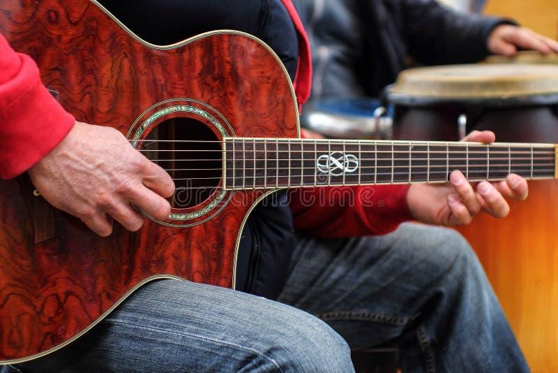 Sirva los juegos en la guitarra acústica - guitarrista imagen de archivo