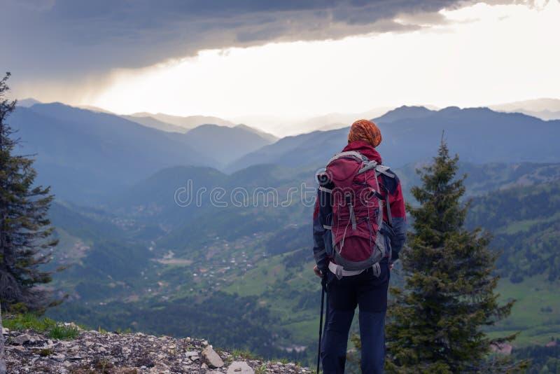 Sirva los soportes del viajero en un acantilado y los relojes la puesta del sol épica fotos de archivo