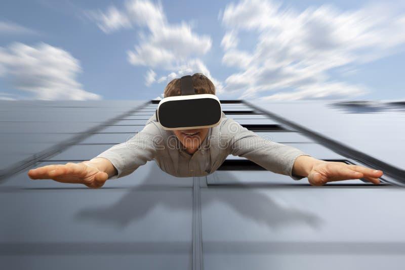 Sirva los vidrios de la realidad virtual que llevan que vuelan de un rascacielos imagenes de archivo