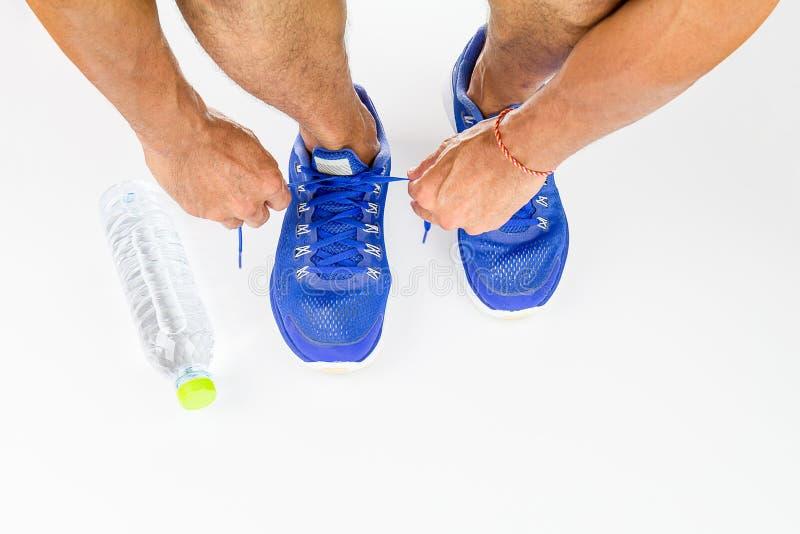 Sirva los zapatos del deporte del cordón con la botella de agua en el fondo blanco imágenes de archivo libres de regalías
