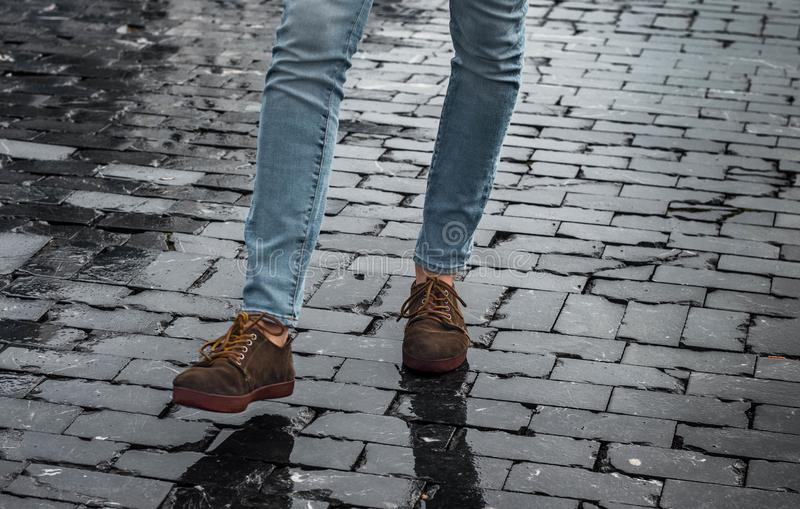 Sirva los zapatos y las piernas marrones del inconformista en la calle con los ladrillos negros que toman una medida fotografía de archivo libre de regalías