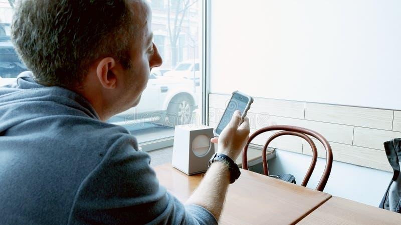 Sirva mandar un SMS y la ojeada con el app móvil en un café imagen de archivo libre de regalías