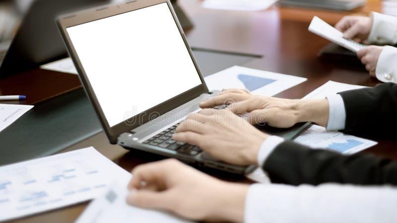 Sirva mecanografiar en el ordenador portátil en la reunión, encargado de equipo que hace la presentación del negocio imagen de archivo libre de regalías