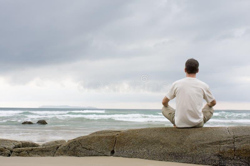 Sirva meditating en una roca en el mar imagen de archivo