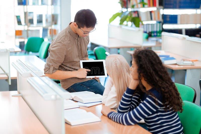 Sirva mostrar algo en la tableta a sus compañeros de clase foto de archivo libre de regalías