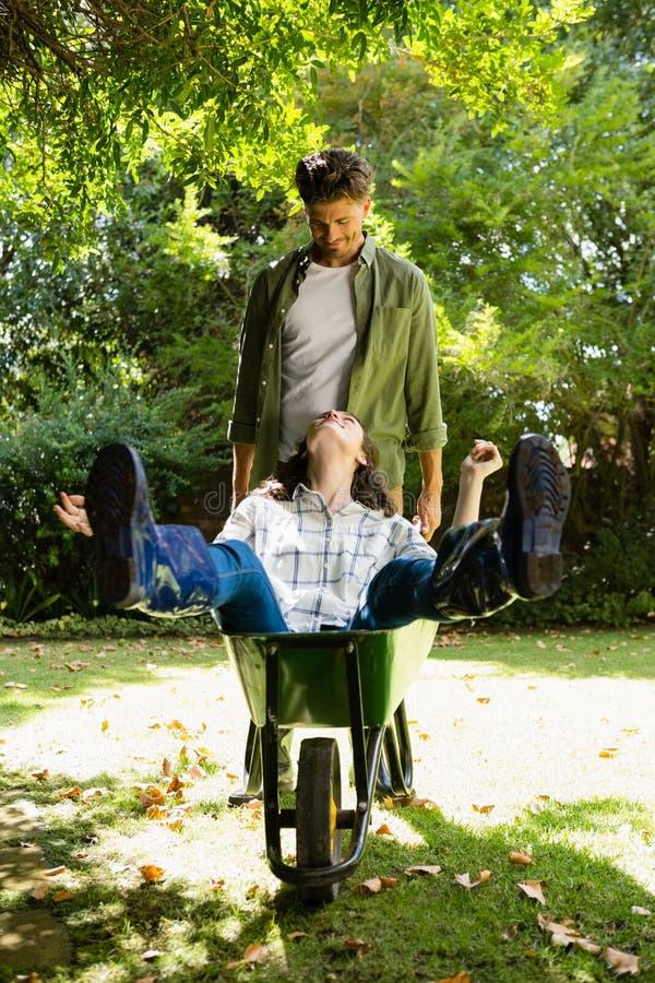 Sirva obrar recíprocamente con la mujer mientras que empuja la carretilla en jardín fotos de archivo
